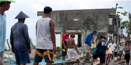 Fisherfolk assess boat damage in San Jose, Leyte. Credit: Oxfam
